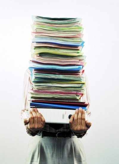 businessman-carrying-pile-of-files-M34903